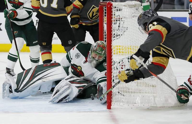 Minnesota Wild goaltender Devan Dubnyk makes a glove save against Vegas Golden Knights right wing Mark Stone, right, during the second period of an NHL hockey game Friday, March 29, 2019, in Las Vegas. (AP Photo/John Locher)