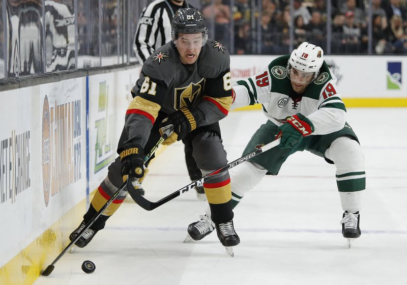 Vegas Golden Knights right wing Mark Stone (61) skates around Minnesota Wild center Luke Kunin (19) during the second period of an NHL hockey game Friday, March 29, 2019, in Las Vegas. (AP Photo/John Locher)