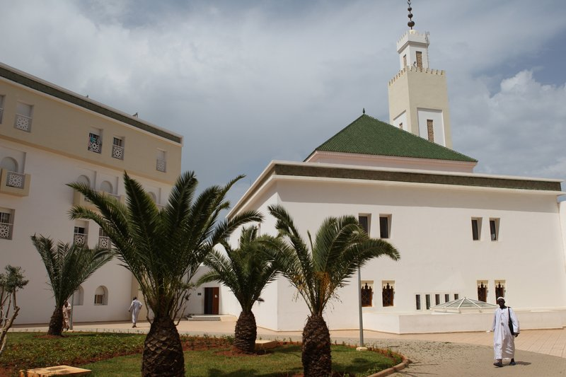 FILE - In this Monday, April 10, 2017 filer, Sub-Saharan students walks next to the mosque at the academy's courtyard where they study religious subjects such as Koranic interpretation, exegesis, Hadith and Sunnah, as well as Islamic law or Shari'a at the Imams' Academy, in Rabat, Morocco. (AP Photo/Abdeljalil Bounhar, File)