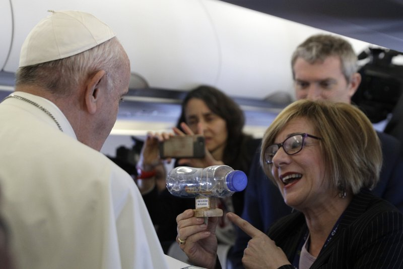Pope Francis is given a plastic bottle containing a ship made by inmates of a Spanish prison with writing reading in Spanish