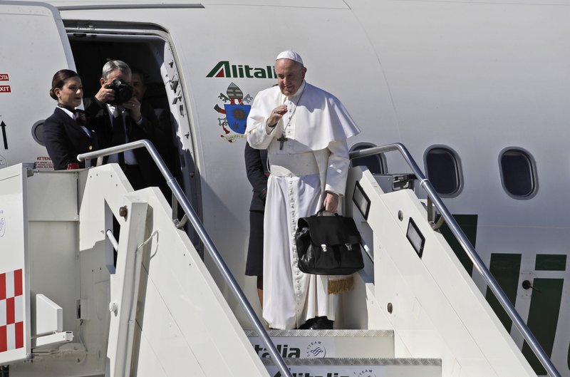 Pope Francis waves as he boards the airplane for Rabat, Morocco at Rome's Fiumicino International airport, Saturday, March 30, 2019. (AP Photo/Alessandra Tarantino)