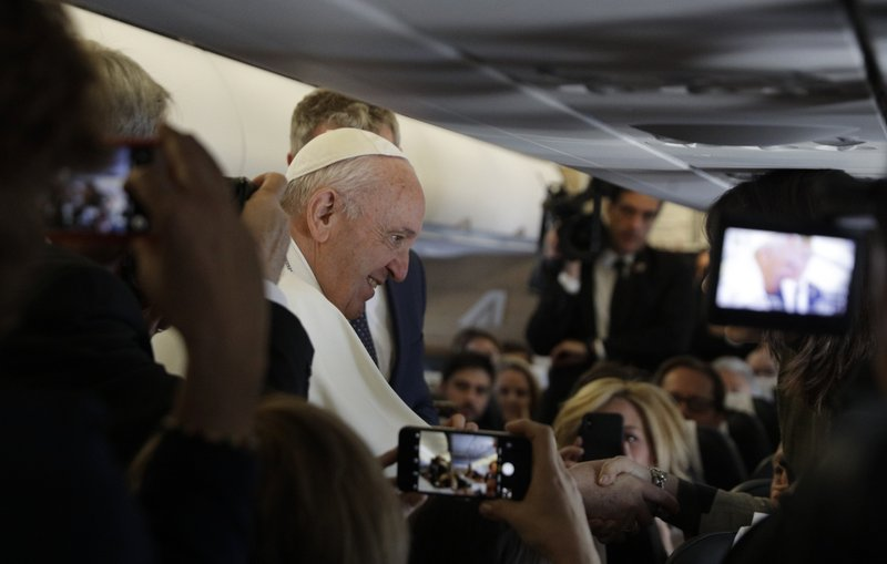 Pope Francis greets reporters during the flight from Rome to Rabat, Morocco, Saturday, March 30, 2019. (AP Photo/Gregorio Borgia, Pool)