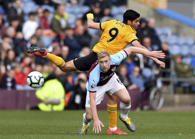 Burnley's Ben Mee, front, and Wolverhampton Wanderers' Raul Jimenez battle for the ball during the English Premier League soccer match between Burnley and Wolverhampton Wanderers at the Turf Moor stadium, Burnley, England. (Anthony Devlin/PA via AP)