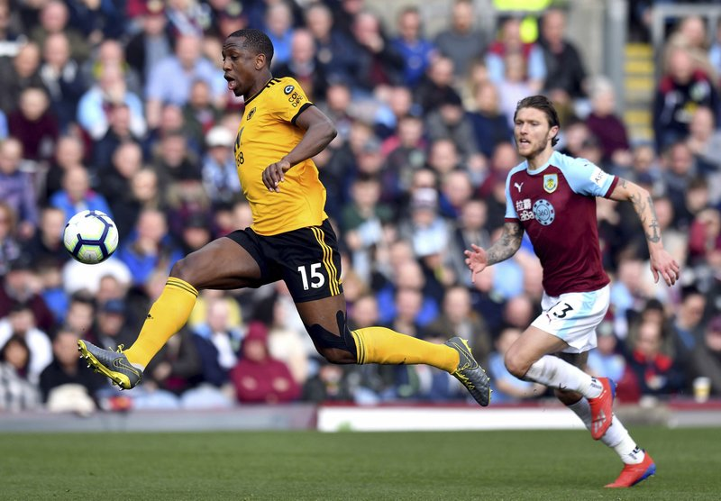 Wolverhampton Wanderers Willy Boly, left, and Burnley's Jeff Hendrick during the English Premier League soccer match between Burnley and Wolverhampton Wanderers at the Turf Moor stadium, Burnley, England. (Anthony Devlin/PA via AP)