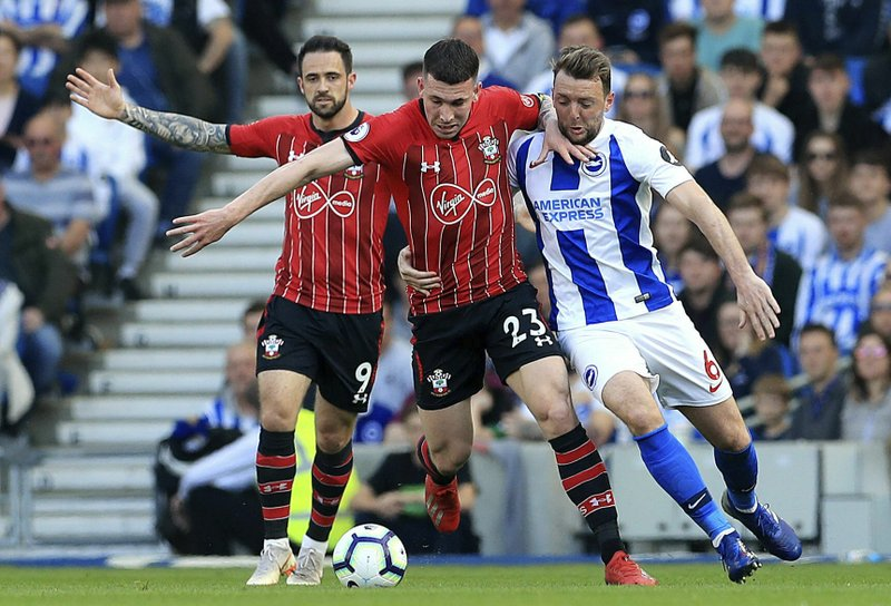 Southampton's Danny Ings, left, Pierre-Emile Hojbjerg, center, and Brighton & Hove Albion's Dale Stephens battle for the ball during the English Premier League soccer match between Brighton and Hove Albion and Southampton at the Amex Stadium, Brighton England. (Gareth Fuller/PA via AP)