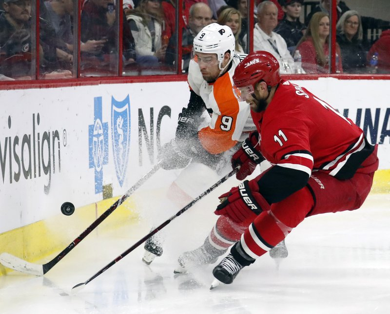 Philadelphia Flyers' Ivan Provorov (9) of Russia and Carolina Hurricanes' Jordan Staal (11) battle for the puck during the third period of an NHL hockey game in Raleigh, N. (AP Photo/Chris Seward)