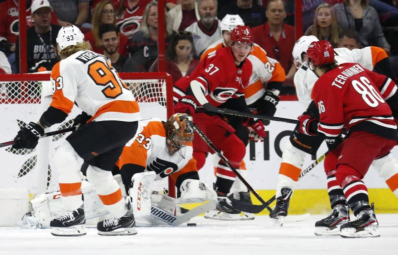 Philadelphia Flyers' Jakub Voracek (93) of the Czech Republic and Cam Talbot (33) defend the net against Carolina Hurricanes' Andrei Svechnikov (37) and Teuvo Teravainen (86) during the first period of an NHL hockey game in Raleigh, N. (AP Photo/Chris Seward)