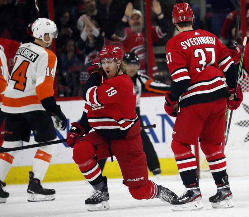 Carolina Hurricanes' Dougie Hamilton (19) celebrates his goal with Andrei Svechnikov (37) of Russia while Philadelphia Flyers' Sean Couturier (14) skates away during the first period of an NHL hockey game in Raleigh, N. (AP Photo/Chris Seward)