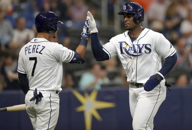 Tampa Bay Rays' Yandy Diaz, right, is congratulated by Michael Perez after scoring on a double by Kevin Kiermaier during the fifth inning of a baseball game against the Houston Astros, Saturday, March 30, 2019, in St. (AP Photo/Mike Carlson)