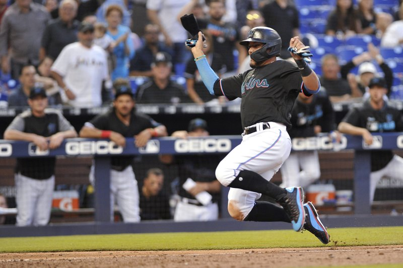 Miami Marlins' Miguel Rojas slides into home to score during the fourth inning of the team's baseball game against the Colorado Rockies in Miami on Saturday, March 30, 2019. (AP Photo/Gaston De Cardenas)