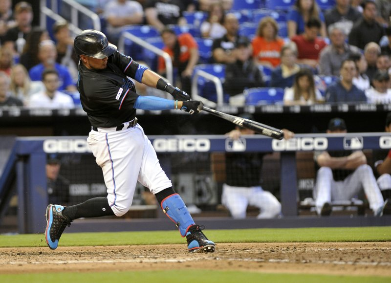 Miami Marlins' Miguel Rojas doubles, driving in a run during the fourth inning of the team's baseball game against the Colorado Rockies in Miami on Saturday, March 30, 2019. (AP Photo/Gaston De Cardenas)