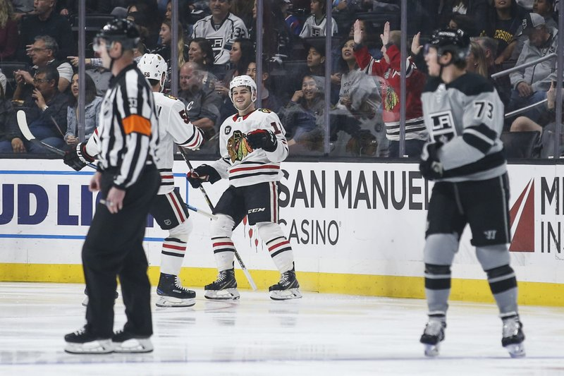 Chicago Blackhawks forward Alex DeBrincat (12) celebrates his goal with defenseman Erik Gustafsson (56) during the second period of the team's NHL hockey game against Los Angeles Kings on Saturday, March 30, 2019, in Los Angeles. (AP Photo/Ringo H.W. Chiu)