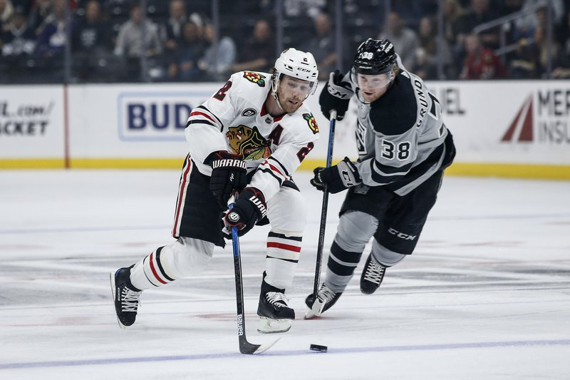 Chicago Blackhawks defenseman Duncan Keith (2) reaches for the puck as Los Angeles Kings forward Carl Grundstrom (38) defends during the first period of an NHL hockey game Saturday, March 30, 2019, in Los Angeles. (AP Photo/Ringo H.W. Chiu)