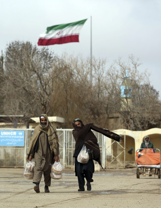 In this Feb. 20, 2019 photo, Afghans return to Afghanistan at the Islam Qala border with Iran, in the western Herat Province. (AP Photo/Rahmat Gul)