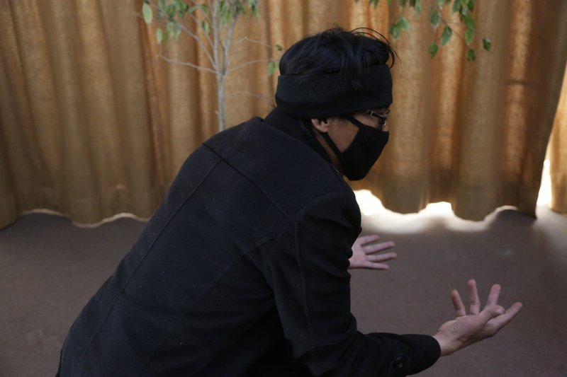 In this Feb. 26, 2019 photo, Abdullah, a former Afghan fighter in Syria with the Fatimiyoun Brigade, wears a mask to hid his identity during an interview with The Associated Press in Kabul, Afghanistan. (AP Photo/Rahmat Gul)