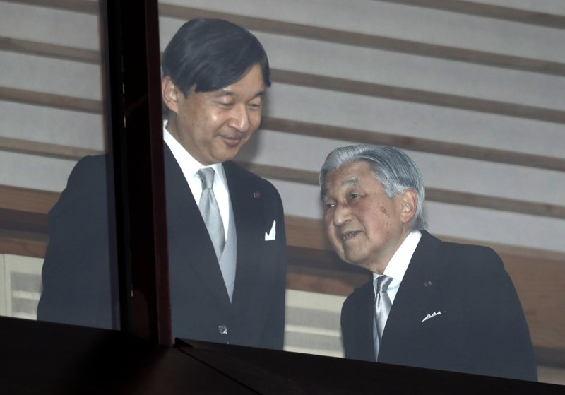 FILE - In this Dec. 23, 2018, file photo, Japan's Emperor Akihito, right, accompanied by Crown Prince Naruhito, walks away after greeting well-wishers when they appeared on the balcony of the Imperial Palace to mark the emperor's 85th birthday in Tokyo. (AP Photo/Eugene Hoshiko, File)