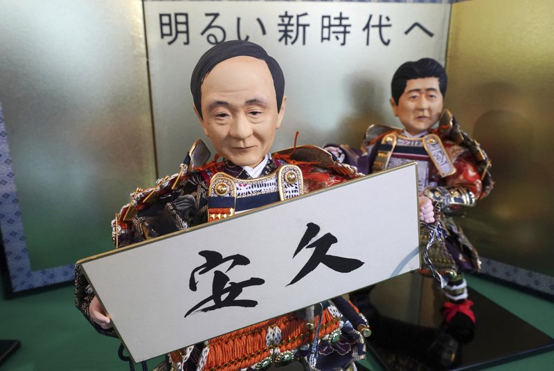 In this Thursday, March 28, 2019, photo, Japanese traditional dolls depicting Japanese Chief Cabinet Secretary Yoshihide Suga holding the new era name