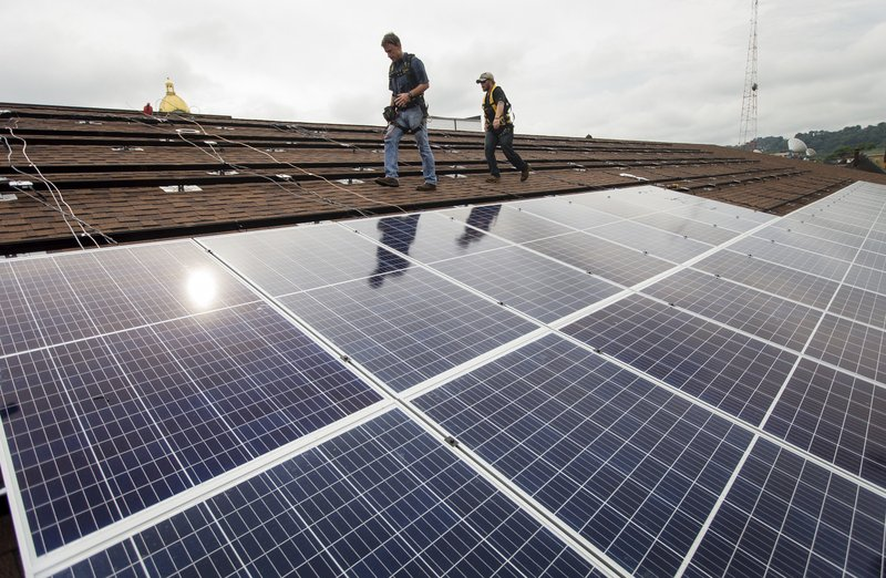 In a Friday, Aug. 3, 2018 photo, Zach Drennen, left, and Colton Memmott of Rewire Appalachia and Coalfield Development install solar panels on the roof of Harmony House as part of a project by Solar Holler, in Huntington, W. (Sholten Singer/The Herald-Dispatch via AP)