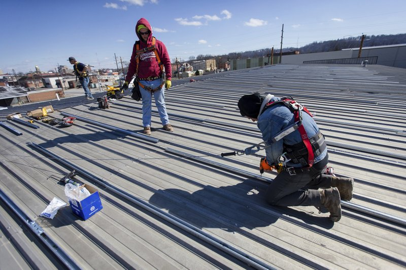 Solar Holler technicians work to install struts to create the frame work that will hold solar panels on Wednesday, March 6, 2019, at the Habitat For Humanity Restore in Huntington. (Sholten Singer/The Herald-Dispatch via AP)