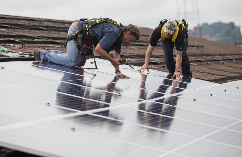 Zach Drennen, left, and Colton Memmott of Rewire Appalachia and Coalfield Development install solar panels on the roof of Harmony House as part of a project by Solar Holler on Friday, Aug. (Sholten SingerThe Herald-Dispatch via AP)