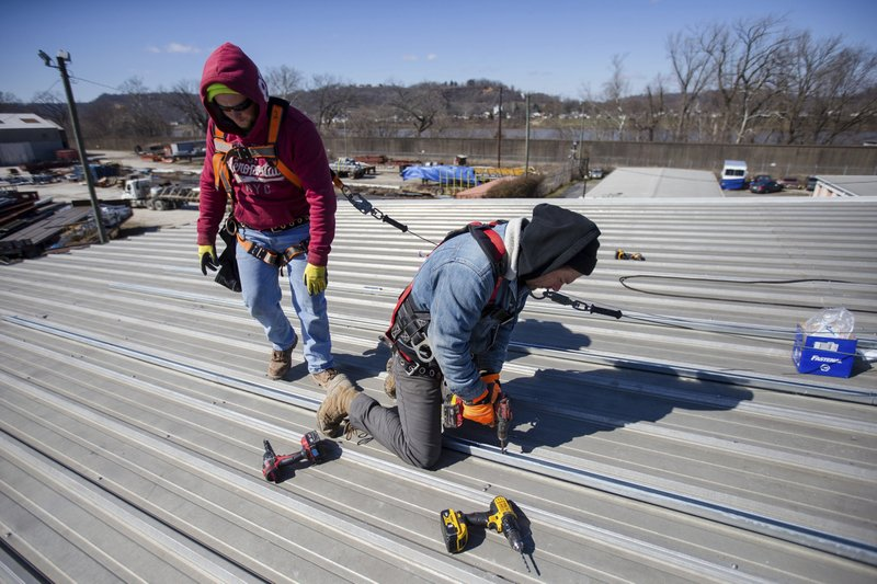 In a Wednesday, March 6, 2019 photo,  Solar Holler technician Joey Chandler, right, and Jacob Dyer work to install struts to create the frame work that will hold solar panels on Wednesday, March 6, 2019, at the Habitat For Humanity Restore in Huntington W. (Sholten Singer/The Herald-Dispatch via AP)