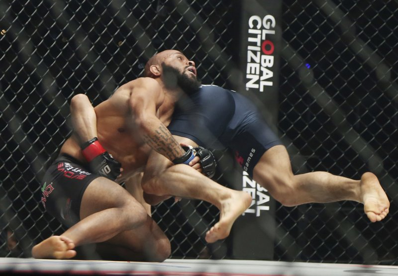 Mixed martial arts (MMA) fighters Demetrious Johnson, left, of the United States and Japan's Yuya Wakamatsu fight during their flyweight world grand prix quarterfinal of One Championship bout in Tokyo, Sunday, March 31, 2019. (AP Photo/Koji Sasahara)