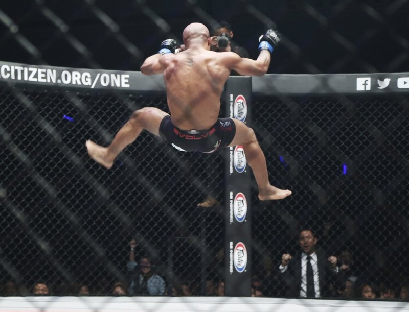 Mixed martial arts (MMA) fighters Demetrious Johnson of the United States celebrates after defeating Japan's Yuya Wakamatsu during their flyweight world grand prix quarterfinal of One Championship bout in Tokyo, Sunday, March 31, 2019. (AP Photo/Koji Sasahara)