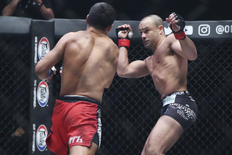 Mixed martial arts (MMA) fighters Russia's Timofey Nastyukhin ,left and Eddie Alvarez of the Unites States fight during their lightweight world grand prix quarterfinal of One Championship bout in Tokyo, Sunday, March 31, 2019. (AP Photo/Koji Sasahara)