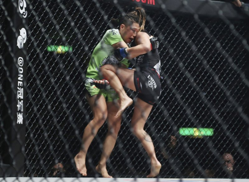 Mixed martial arts (MMA) fighters China's Xiong Jingnan, left, and Angela Lee of Singapore fight during One Championship bout in Tokyo, Sunday, March 31, 2019. (AP Photo/Koji Sasahara)