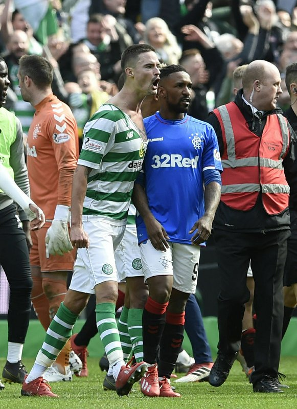 Celtic's Mikael Lustig with his shirt torn protests, with Rangers Jermain Defoe, centre right, during their Scottish Premiership soccer match at Celtic Park in Glasgow, Scotland, Sunday March 31, 2019. (Ian Rutherford/PA via AP)