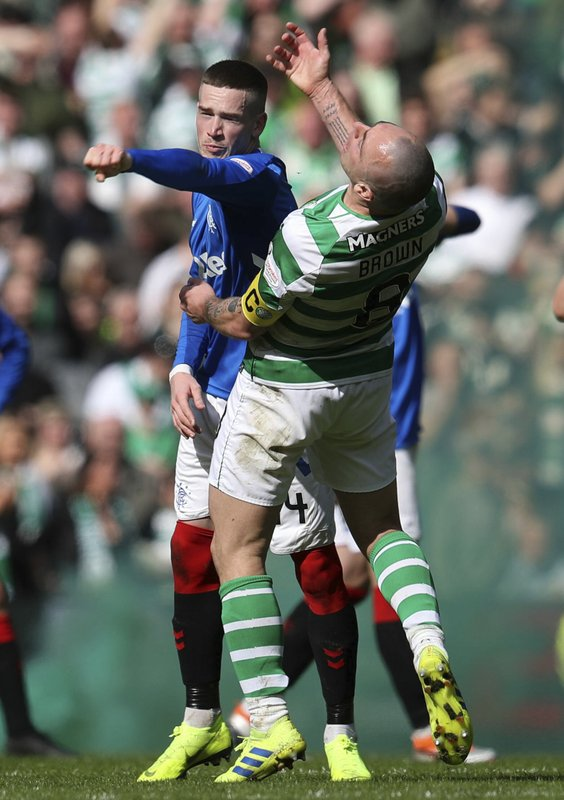 Rangers' Ryan Kent, left, and Celtic's Scott Brown clash during their Scottish Premiership soccer match at Celtic Park in Glasgow, Scotland, Sunday March 31, 2019. (Andrew Milligan/PA via AP)