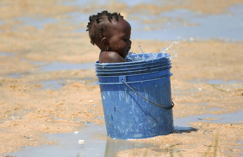 A baby plays with water in a bucket at a camp for displaced survivors of Cyclone Idai in Beira, Mozambique, Sunday, March, 31, 2019. (AP Photo/Tsvangirayi Mukwazhi)