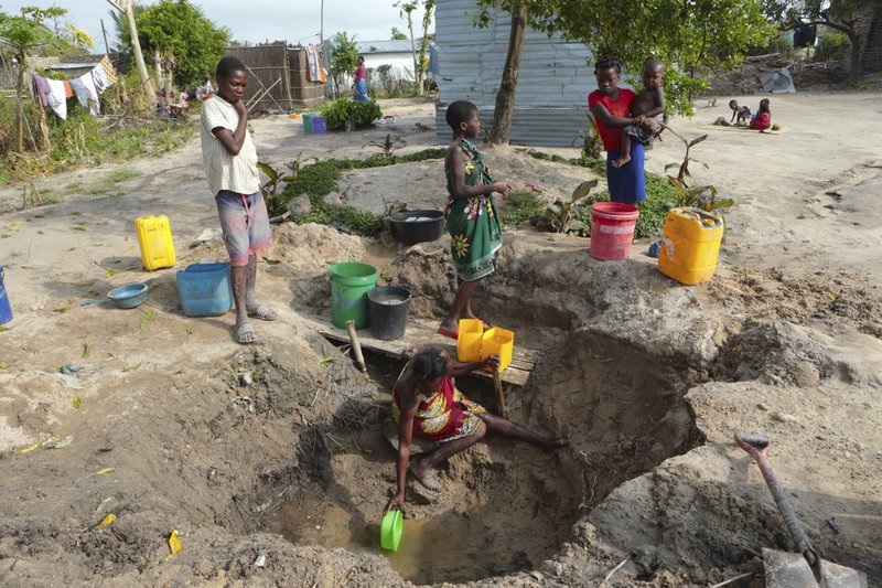 A woman fetches water from an unprotected source in Beira, Mozambique, Sunday, March, 31, 2019. Cholera cases among cyclone survivors in Mozambique have jumped to 271, authorities said. (AP Photo/Tsvangirayi Mukwazhi)