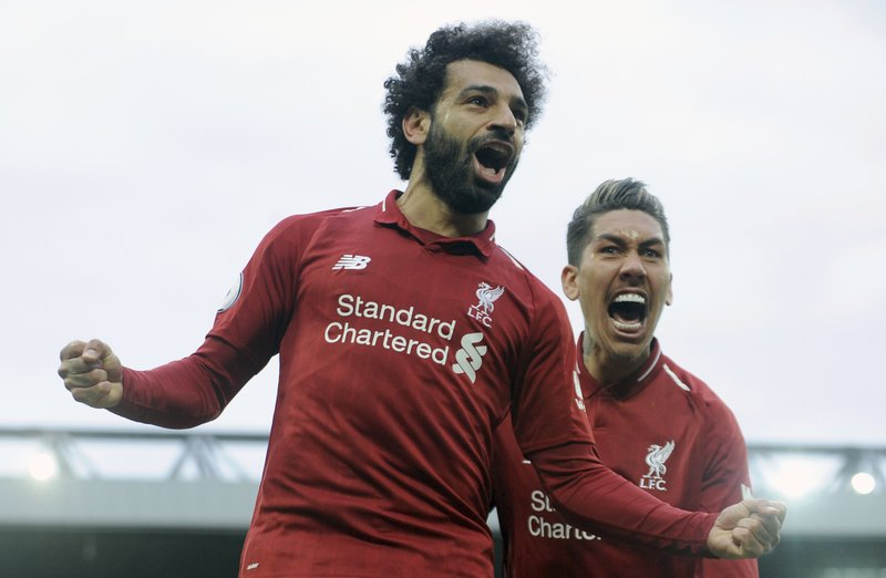Liverpool's Mohamed Salah, left, and Liverpool's Roberto Firmino celebrate after Tottenham's Toby Alderweireld scores an own goal past his goalkeeper during the English Premier League soccer match between Liverpool and Tottenham Hotspur at Anfield stadium in Liverpool, England, Sunday, March 31, 2019. (AP Photo/Rui Vieira)