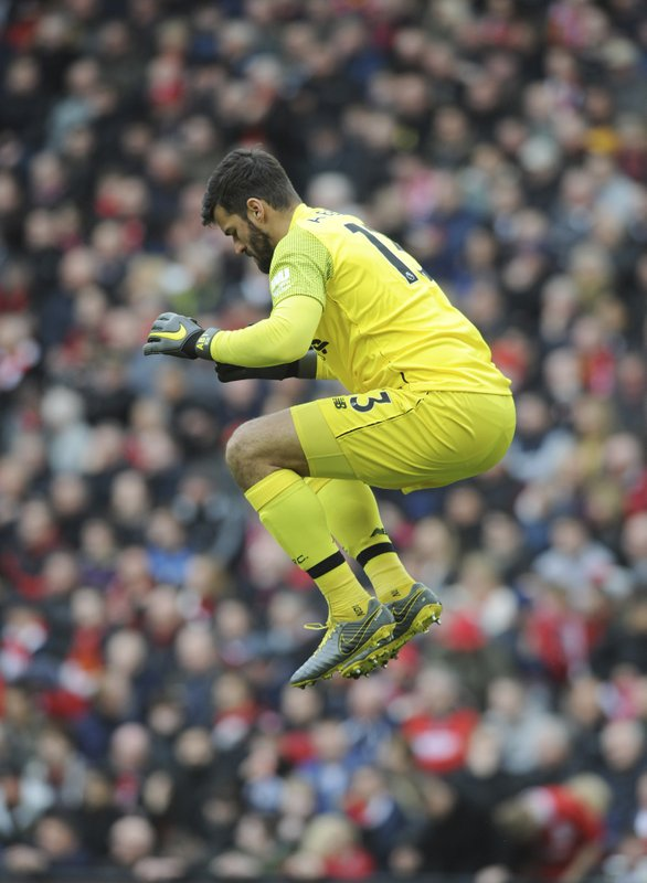 Liverpool goalkeeper Alisson Becker jumps during the English Premier League soccer match between Liverpool and Tottenham Hotspur at Anfield stadium in Liverpool, England, Sunday, March 31, 2019. (AP Photo/Rui Vieira)