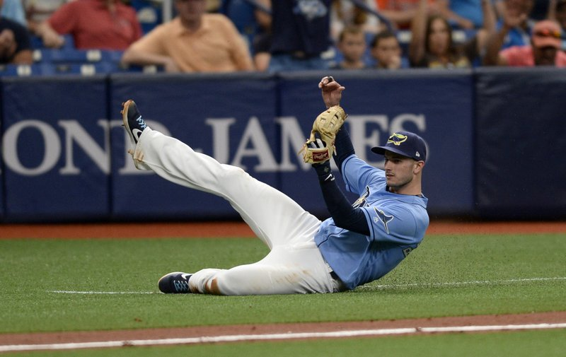 Tampa Bay Rays third baseman Daniel Robertson (28) makes a catch in foul territory for the final out of a baseball game during the ninth inning against the Houston Astros, Sunday, March 31, 2019, in St. (AP Photo/Jason Behnken)
