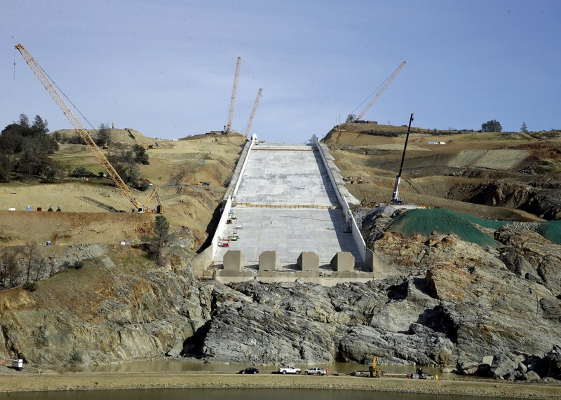 FILE - In this Nov. 30, 2017, file photo, Cranes sit on the sides of the Oroville Dam spillway in Oroville, Calif. (AP Photo/Rich Pedroncelli, File)