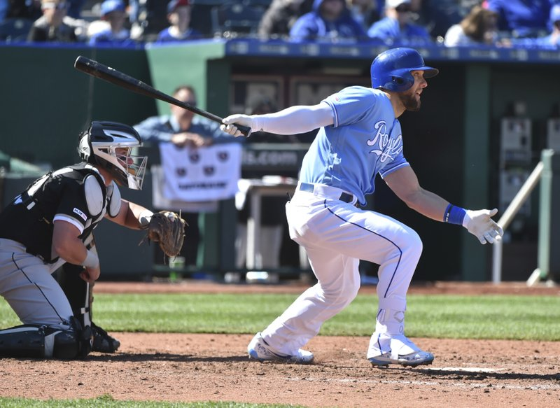 Kansas City Royals' Alex Gordon, right, singles in the seventh inning during a baseball game against the Chicago White Sox, Sunday, March 31, 2019, in Kansas City, Mo. (AP Photo/Ed Zurga)