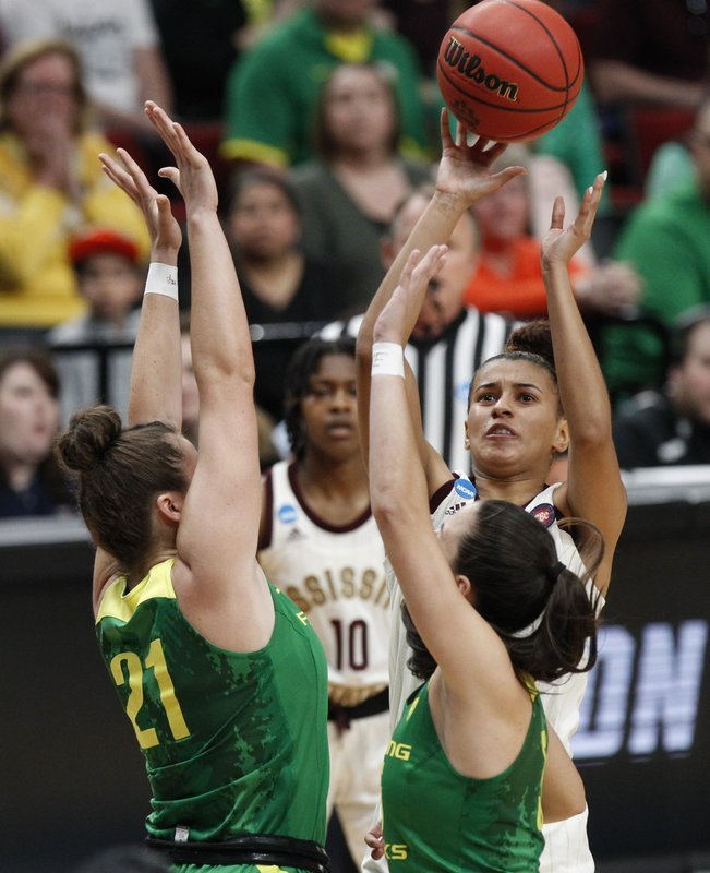 Mississippi State guard Andra Espinoza-Hunter, right, shoots over Oregon forward Erin Boley, left, and guard Maite Cazorla,  front right, during the first half of a regional final in the NCAA women's college basketball tournament Sunday, March 31, 2019, in Portland, Ore. (AP Photo/Steve Dipaola)
