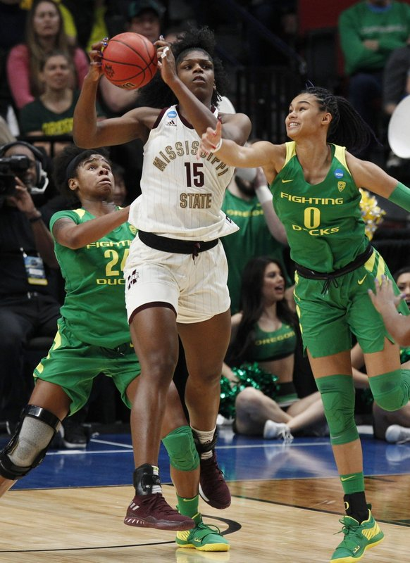 Mississippi State center Teaira McCowan, center, pulls down a rebound as Oregon forwards Ruthy Hebard, left, and Satou Sabally, right defend during the first half of a regional final in the NCAA women's college basketball tournament Sunday, March 31, 2019, in Portland, Ore. (AP Photo/Steve Dipaola)