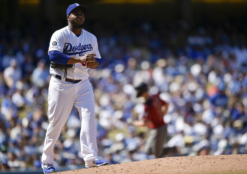 Los Angeles Dodgers pitcher Pedro Baez, left, reacts after allowing a two-run home run to Arizona Diamondbacks' Luke Weaver during the fourth inning of an MLB baseball game in Los Angeles, Sunday, March 31, 2019. (AP Photo/Kelvin Kuo)