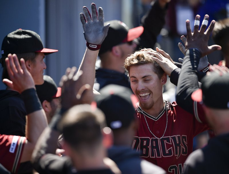 Arizona Diamondbacks' Luke Weaver celebrates with the dugout after hitting a two-run home run during the fourth inning of a baseball game against the Los Angeles Dodgers in Los Angeles, Sunday, March 31, 2019. (AP Photo/Kelvin Kuo)