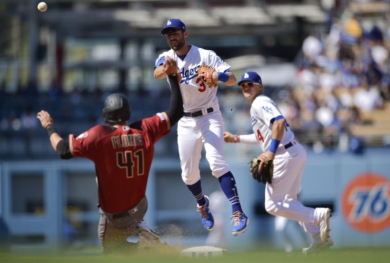 Los Angeles Dodgers shortstop Chris Taylor, center, throws to first after forcing out Arizona Diamondbacks' Wilmer Flores, left, to complete a double play during the fourth inning of a baseball game as Enrique Hernandez looks on in Los Angeles, Sunday, March 31, 2019. (AP Photo/Kelvin Kuo)