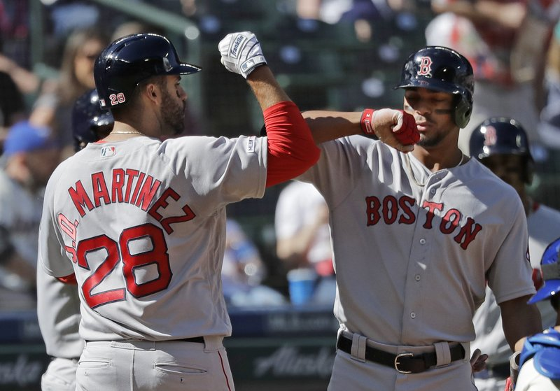 Boston Red Sox's J.D. Martinez, left, is greeted by Xander Bogaerts, right, after hitting a three-run home run during the fourth inning of a baseball game against the Seattle Mariners, Sunday, March 31, 2019, in Seattle. (AP Photo/Ted S. Warren)
