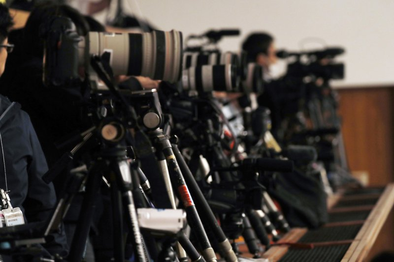 Cameramen stand by for a planned press conference by Chief Cabinet Minister Yoshihide Suga at prime minister's official residence in Tokyo Monday, April 1, 2019. (AP Photo/Eugene Hoshiko)