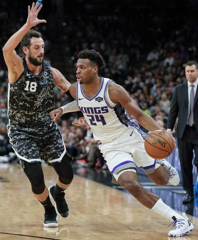 Sacramento Kings' Buddy Hield (24) drives against San Antonio Spurs' Marco Belinelli during the first half of an NBA basketball game, Sunday, March 31, 2019, in San Antonio. (AP Photo/Darren Abate)