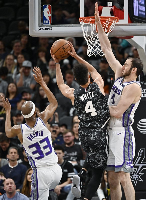 San Antonio Spurs' Derrick White (4) shoots against Sacramento Kings' Kosta Koufos, right, and Corey Brewer during the first half of an NBA basketball game, Sunday, March 31, 2019, in San Antonio. (AP Photo/Darren Abate)