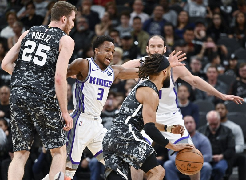 San Antonio Spurs' Patty Mills, front right, drives around Sacramento Kings' Yogi Ferrell (3) as he is screened by Spurs' Jakob Poeltl (25) during the first half of an NBA basketball game, Sunday, March 31, 2019, in San Antonio. (AP Photo/Darren Abate)