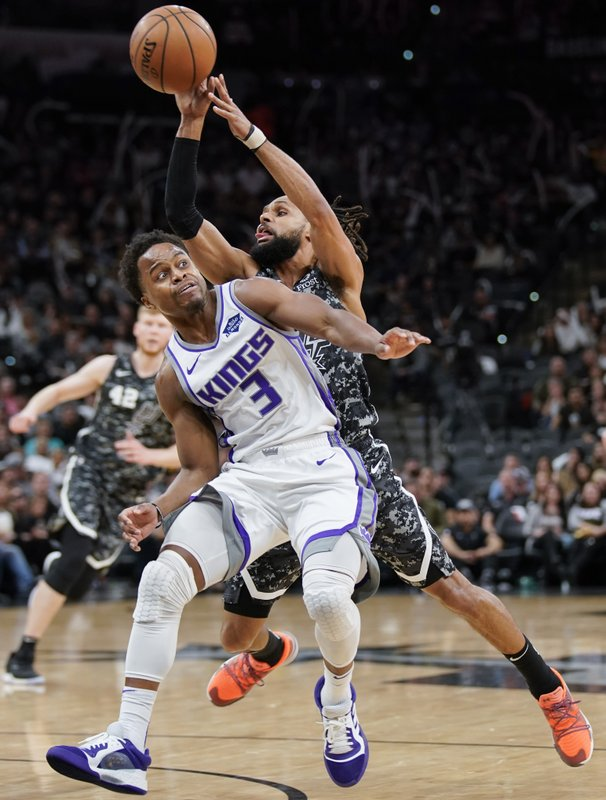 San Antonio Spurs' Patty Mills, right, looks to pass as he collides with Sacramento Kings' Yogi Ferrell during the second half of an NBA basketball game, Sunday, March 31, 2019, in San Antonio. (AP Photo/Darren Abate)