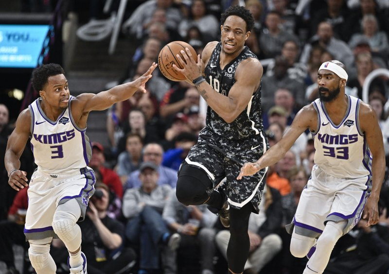 San Antonio Spurs' DeMar DeRozan, center, attempts to evade Sacramento Kings' Yogi Ferrell, left, and Corey Brewer, right, during the second half of an NBA basketball game, Sunday, March 31, 2019, in San Antonio. (AP Photo/Darren Abate)